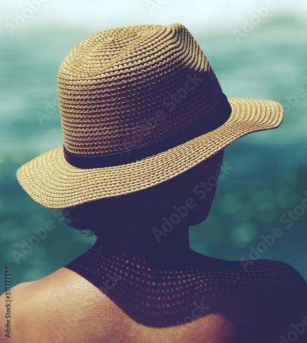 Fotografia Rear View Of Woman Wearing Hat Against Sea