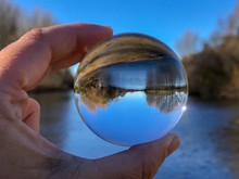 Close-Up Of Hand Holding Crystal Ball Against River