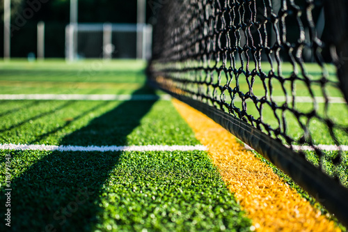 Close-Up Of Net On Playing Field During Sunny Day - fototapety na wymiar