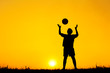 Silhouette Boy Playing With Ball While Standing On Field Against Orange Sky