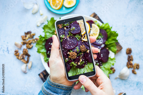 Fototapeta Woman take picture of vegan food with phone at her kitchen. Hand make a closeup smartphone photo of beetroot salad with walnuts for blogging or social media content. Vegetarian healthy food. obraz