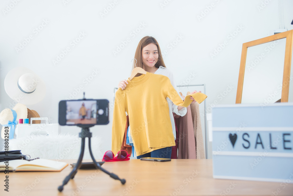 Fototapeta Beautiful asian woman blogger showing clothes in front of camera to recording vlog video live streaming at her shop.Business online influencer on social media concept.