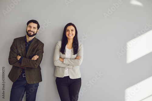 Fototapeta A businessman and a business woman are standing against a gray wall obraz