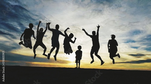Fototapety, obrazy: Boy Amidst Silhouette Friends Jumping On Field Against Cloudy Sky