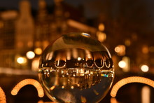 Close-Up Of Crystal Ball Against Illuminated Buildings In City At Night