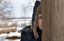Close-Up Of Boy Wearing Fur Hat Standing Behind Wooden Fence During Winter
