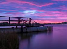 Footbridge Over Lake Against Dramatic Sky During Sunset
