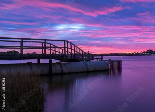Photo Footbridge Over Lake Against Dramatic Sky During Sunset
