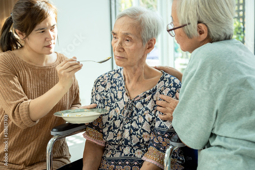 Fotomural Asian woman feeding tired senior patient,anorexia,eat less food,depressed female