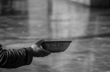Cropped Image Of Beggar Holding Wicker Bowl