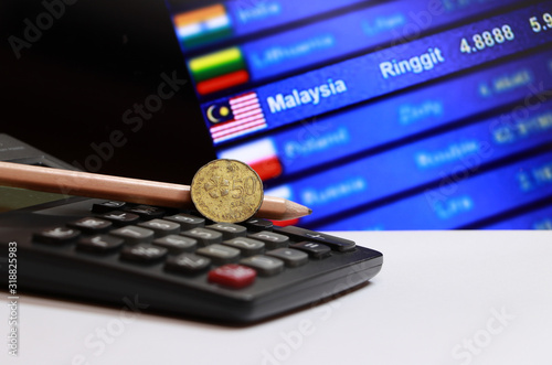 Fotomural Fifty cents coin of Malaysia and pencil on the calculator with digital board of currency exchange money background