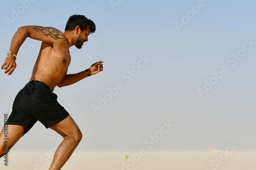 Side View Of Shirtless Young Man Running On Beach Against Sky During Sunny Day Wallpaper Mural