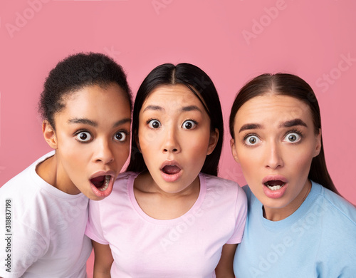 Three Surprised Girls Looking At Camera Posing On Pink Background Wallpaper Mural