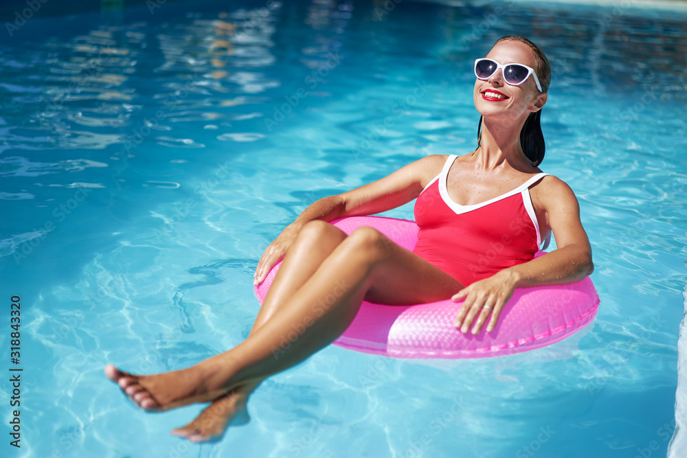 Fototapeta Enjoying suntan and vacation. Outdoor portrait of pretty young woman in red swimsuit with inflatable ring in swimming pool.