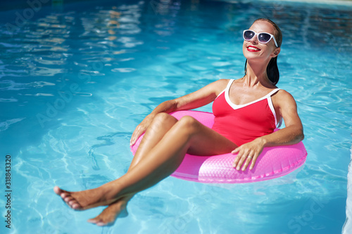 Fototapeta Enjoying suntan and vacation. Outdoor portrait of pretty young woman in red swimsuit with inflatable ring in swimming pool. obraz