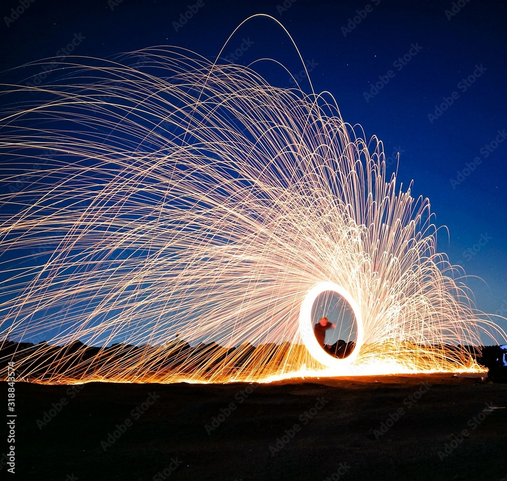 Fototapeta Man Spinning Illuminated Wire Wool Against Sky During Dusk
