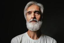 Studio Portrait Of Frowning Senior Man With Gray Beard.