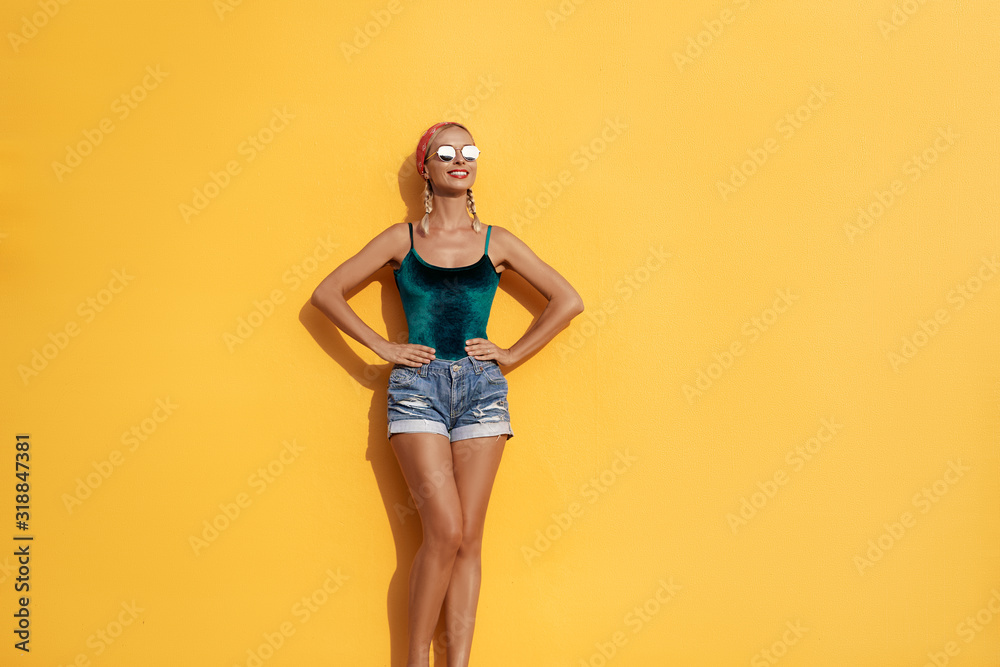 Fototapeta Summer urban fashion. Fun and colorful. Young pretty happy woman in shorts posing against yellow wall.