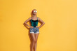 Summer urban fashion. Fun and colorful. Young pretty happy woman in shorts posing against yellow wall.