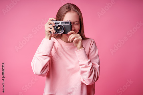 Obraz Traveler and photographer. Studio portrait of pretty young girl holding photocamera. Pink blackground. - fototapety do salonu
