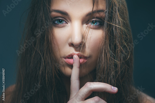 Fotografiet fashion model with beautiful eyes holding finger on her lips
