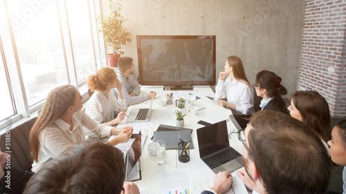 Wideokonferencja biznesowa. Zespół firmy patrząc na ekran