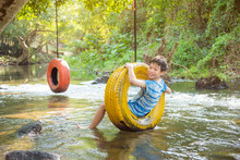Boy Swinging On Tire Over River At Forest
