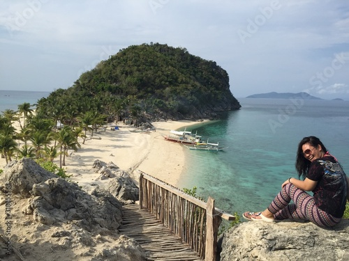 Photo Cheerful Woman Sitting On Rock By Sea Against Sky
