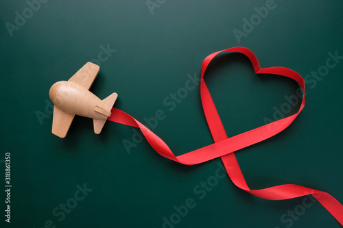 Fototapeta small wooden toy airplane lucky with red ribbon in the shape of heart obraz
