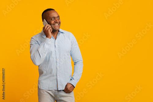 Fotografia Positive mature afro man talking on cellphone