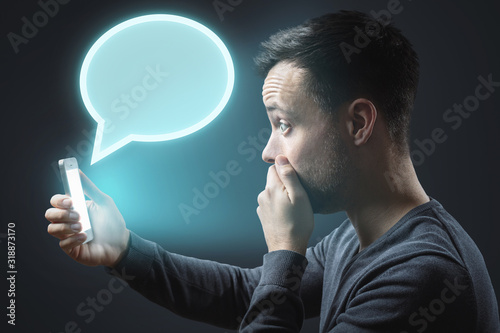 Photo Appalled man getting a message on his smartphone