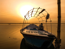 Fisherman Sitting On Boat Moored At Beach Against Orange Sky