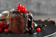 Delicious warm chocolate lava cake with berries on plate, closeup