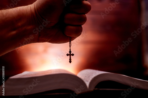 A hand holds a church cross over a bible on a background glowing behind Fototapeta