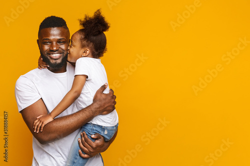 Obraz Preschool black girl kissing smiling father over yellow background - fototapety do salonu