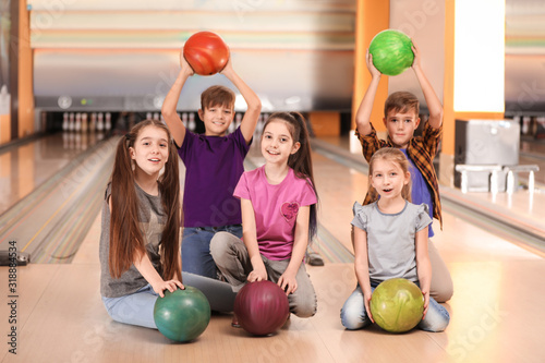 Foto Happy children with balls in bowling club