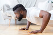 Young black man doing push ups, side view