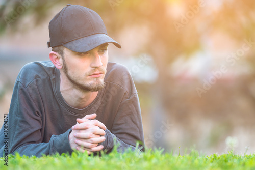 Thoughtful Young Man Lying On Field