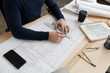 Architect working in office with blueprints.Engineer inspect architectural plan, sketching a construction project.Portrait of handsome bearded man sitting at workplace. Business construction concept.