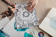 High Angle View Of Watercolor Paintings With Zodiac Signs On Cards And Astrologer Drawing Birth Chart At Table