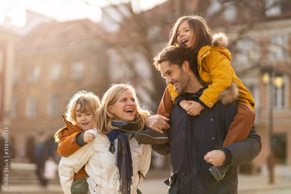 Fototapeta Affectionate young family enjoying their day in a city
