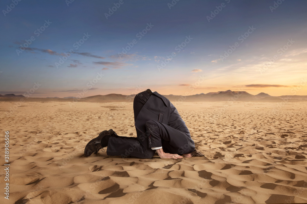 Fototapeta Desparate businessman hiding head in the sand at the desert with copy space