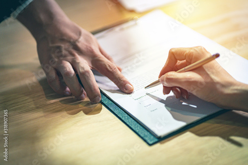 Cuadros en Lienzo Closeup female hand signing a contract investment professional document agreement on the table with pen