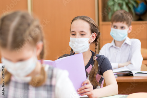 Leinwand Poster Pupils wearing protection mask to prevent virus during lesson in classroom in sc