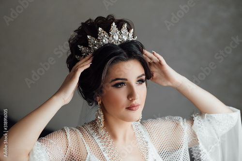 Fashion photo of beautiful bride with dark hair in elegant wedding dress posing in room in the wedding morning. Wedding decoration. The bride touches the crown. Morning of beautiful bride.