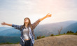 Young Female Hiker With Arms Outstretched Standing On Mountain Against Sky