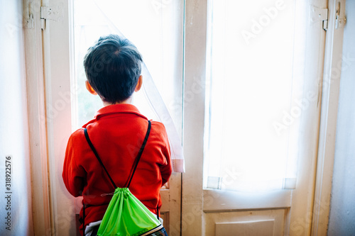 Valokuva child with backpack looks out the window at home