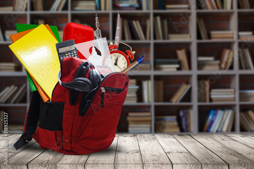 Photo Backpack with school supplies on wooden table, on wall background