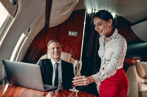 Stewardess and businessman in private jet Wallpaper Mural