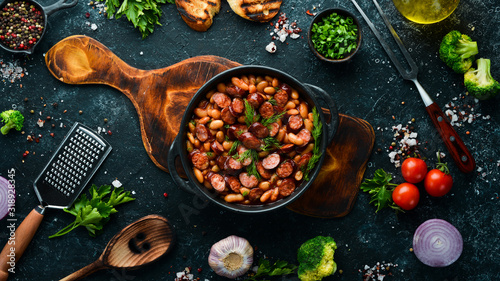 Fototapeta Beans with sausages in tomato sauce on a black plate.  Top view. Free space for your text. obraz